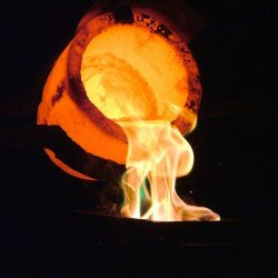 Heated crucible pouring fiery gold, molten metal on a black background